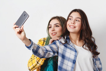 two young women taking selfie with mobile phone. on white