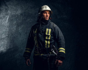 Studio portrait of firefighter dressed in uniform and safety helmet looking sideways with a confident look