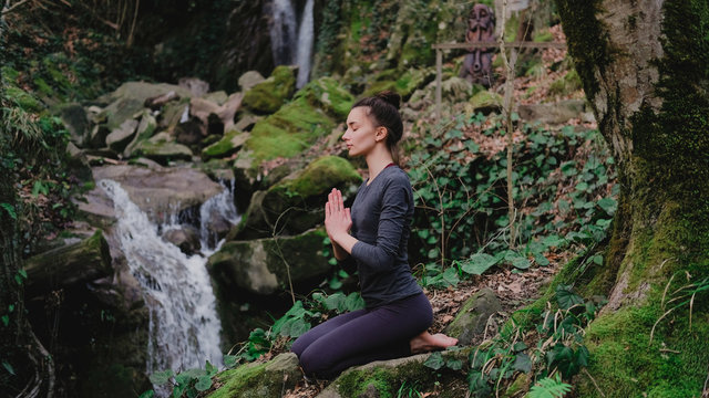 Young slim woman practicing yoga outdoors in moss forest on background of waterfall. Unity with nature concept. Girl meditates sitting