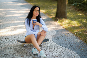 Portrait of a beautiful girl in a white shirt and shorts drinking coffee while sitting on a skateboard in the park on a summer morning