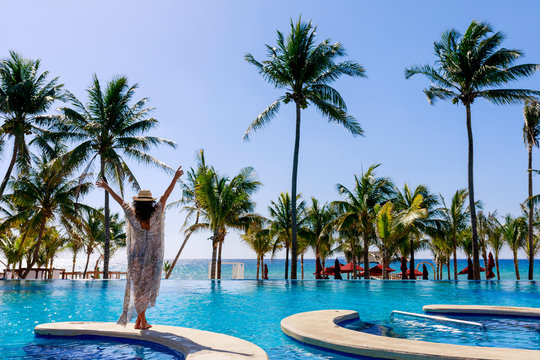 woman by swimming pool in tropical resort
