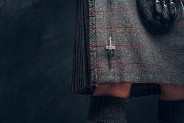 Close-up photo of a traditional Scottish costume against a dark textured wall. Kilt and sporran.