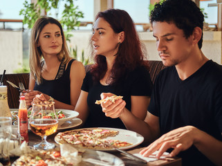 Young friends enjoying pizza and salad in a outdoor cafe