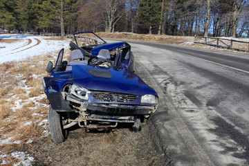 Front of blue car damaged by crash accident on side of the road