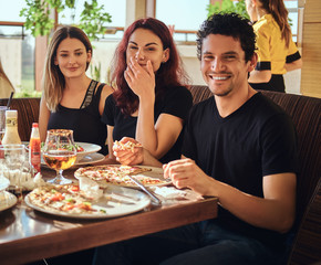 Food and people concept. Cheerful young friends enjoying food and having fun together in the restaurant or cafe outdoor