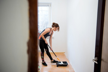 Young woman painting walls with a roller in a new house. Interior design. Renovation