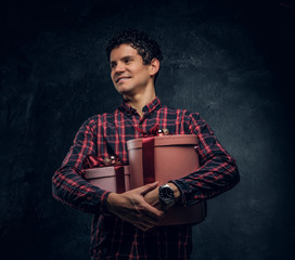 Happy man wearing checkered shirt holding gift boxes in a studio against the background of the dark wall