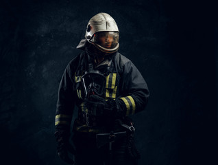 Portrait of a male in full firefighter equipment. Studio photo against a dark textured wall
