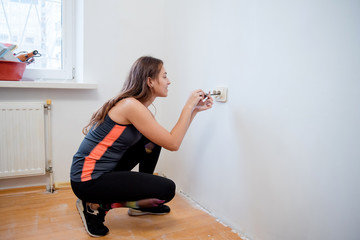 Young brunette woman repairs an electric socket with a screwdriver. Installingnew socket into the wall