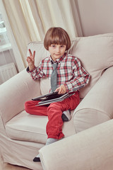 Cute Caucasian schoolboy wearing a checkered shirt with tie showing peace sign and holding a tablet while sitting on a couch at home