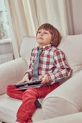 Young schoolboy wearing a checkered shirt with tie holding a digital tablet while sitting on a couch with a strange look at home.