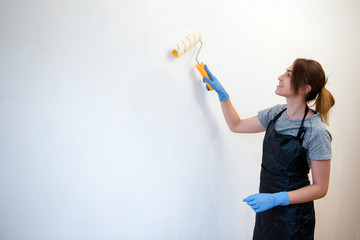 Young attractive woman in apron painting walls with a roller in a new house. Interior design. Renovation