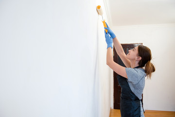 Side view of woman in a robe painting walls with a roller in a new house. Interior design. Renovation. Applying white paint