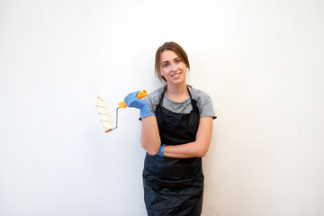 Portrait of beautiful woman in apron painting walls with a roller in a new house. Interior design. Renovation. Smiling at the camera