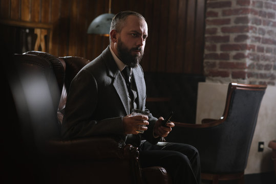 Portrait of serious bearded man with pipe holding glass of whiskey wearing suit and sitting on a big arm chair