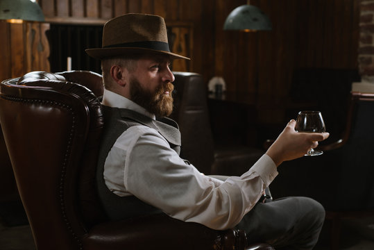 A man in hat wearing vintage suit holding pipe and glass of whiskey sitting on a big chair