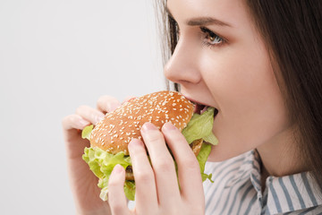 Young beautiful brunette girl on a white background with a hamburger in her hands. Eating with pleasure fast food.