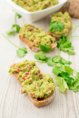 Fresh avocado cream or guacamole on wholemeal slices, healthy breakfast concept.