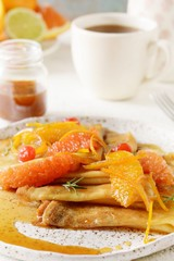Pancakes crepe Suzette for breakfast with orange caramel sauce, orange slices, lime and orange zest and a cup of coffee. Dessert French cuisine. Sunday breakfast