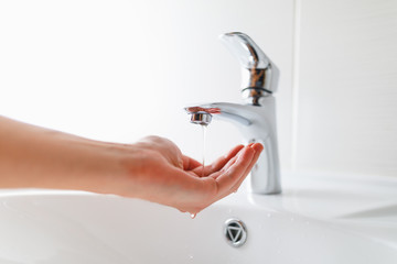 hand under faucet with low pressure water stream