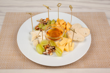 Cheese platter with honey and grapes on a white plate.