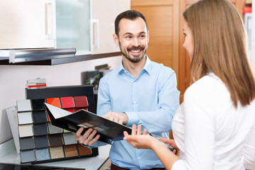 Competent seller consulting female customer in store of kitchen furnishing and appliances
