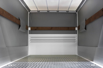 Empty cargo truck, van inside, fragment of commercial transport, vehicle detail with steel floor and gray tarpaulin walls, delivery service concept