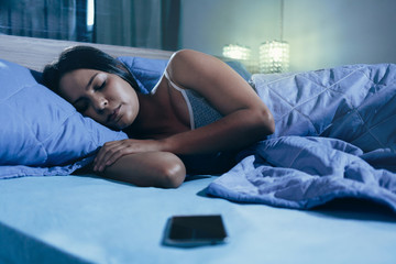 technology and people concept - young woman with smartphone sleeping in bed at home at night