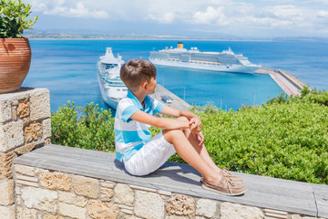 Little boy looking at a cruise ship in the lagoon Mediterranean Sea, Greece