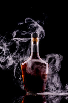 bottle and glass of whiskey or cognac with smoke on dark background