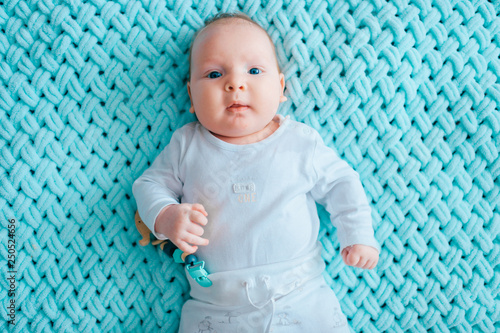 Adorable lovely newborn male baby with blue eyes lifestyle indoor portrait from above. Cute child