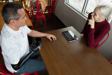 Man with robotic arm talks with woman