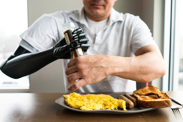 Man uses his robotic arm to open bottle