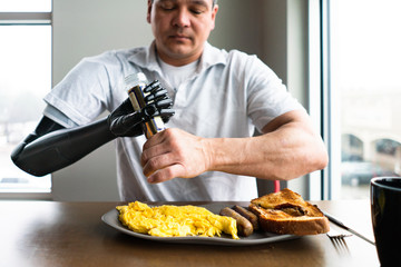 Man uses robotic arm to open bottle