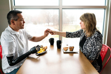 Husband with a robotic arm eats breakfast with his wife
