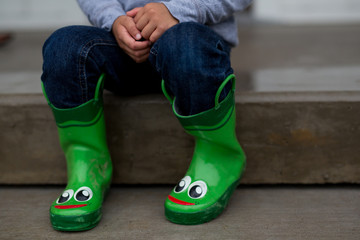 Toddler wears green rubber rain boots with smiley faces