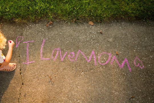 Child writes I Love Mom on sidewalk
