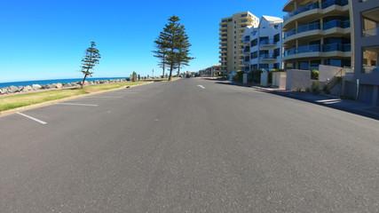 Vehicle POV, driving along the Esplanade in Glenelg, seaside suburb of Adelaide South Australia.