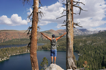 Rear view of man with arms outstretched looking at lake while standing on rock against cloudy sky