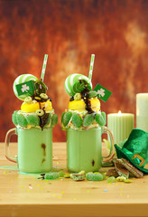 Happy St Patrick's Day on-trend holiday freak shakes milkshakes decorated with candy and lollipops, vertical with copy space.