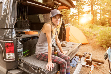 Portrait of smiling woman with beer bottle sitting on car trunk against trees in forest
