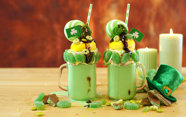 Happy St Patrick's Day on-trend holiday freak shakes milkshakes decorated with candy and lollipops with copy negative space.