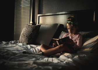 Cute girl reading book while sitting on bed at home