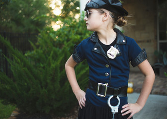 Confident girl wearing police costume with hands on hip standing against plants in yard during Halloween