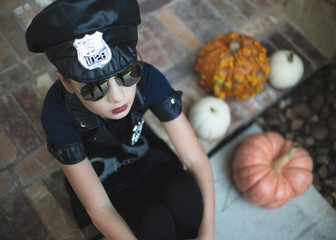 High angle view of girl wearing police costume and sunglasses while sitting by squashes in yard during Halloween