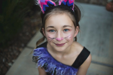 High angle portrait of girl with face paint wearing Halloween costume while sitting in yard during sunset