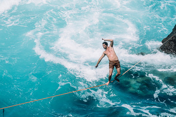 Carefree young man slacklining on rope over sea during sunny day