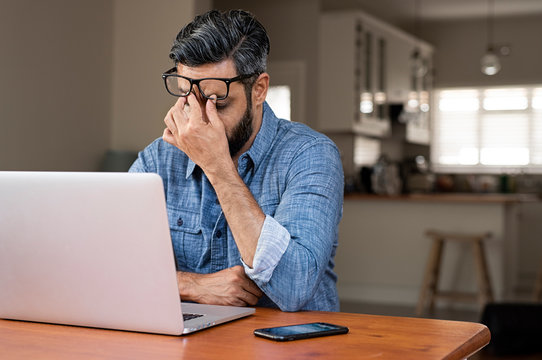 Stressed businessman with laptop computer on wooden table sitting at home