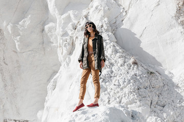 Portrait of woman wearing sunglasses standing on snow covered rock during sunny day