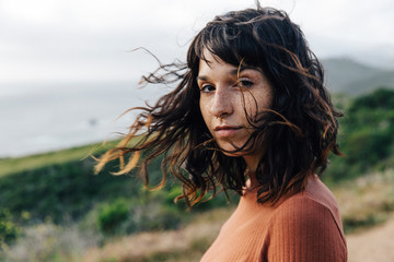 Portrait of confident woman with freckles standing against sky